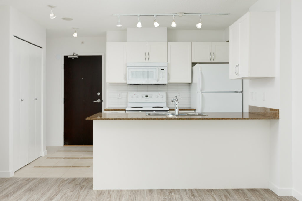 Kitchen with white cabinetry inside Vancouver rental condo.