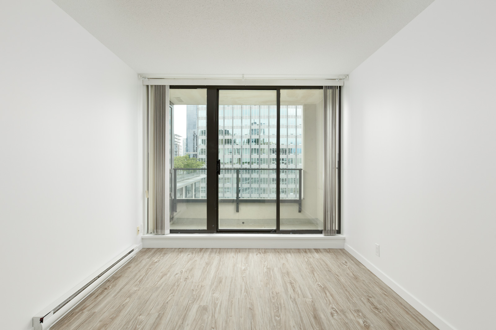 Bedroom with sliding door leading out to balcony of Downtown Vancouver rental condo.
