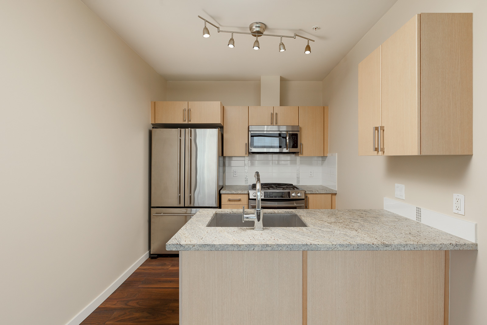 Kitchen with stainless steel appliances and sand coloured cabinetry inside Vancouver luxury condo..