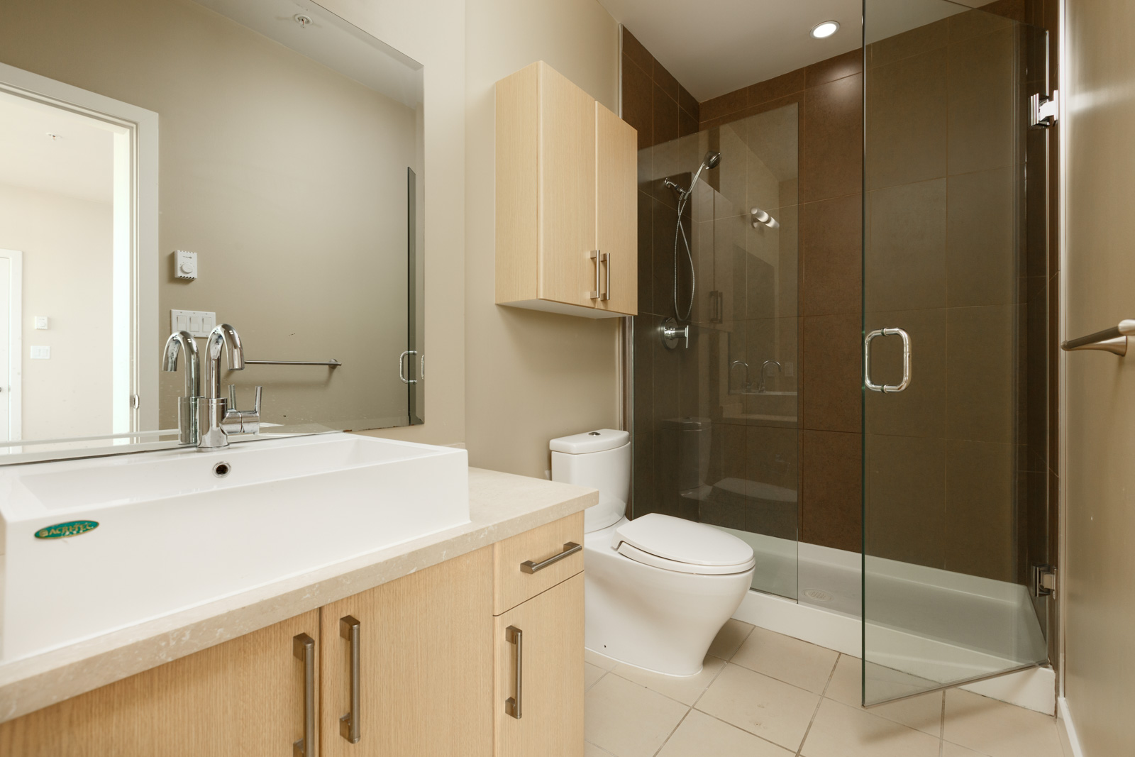 Bathroom with sand coloured hardwood cabinetry and white counter tops inside Vancouver luxury rental condo.