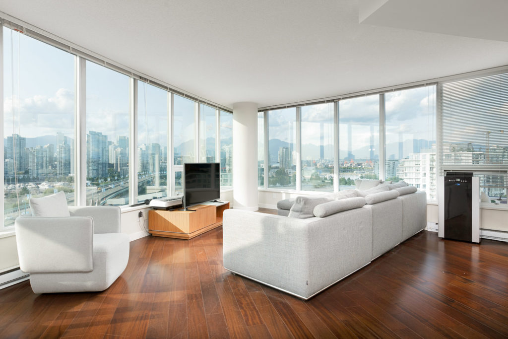 Living room white couches overlooks city skyline from Vancouver rental condo.