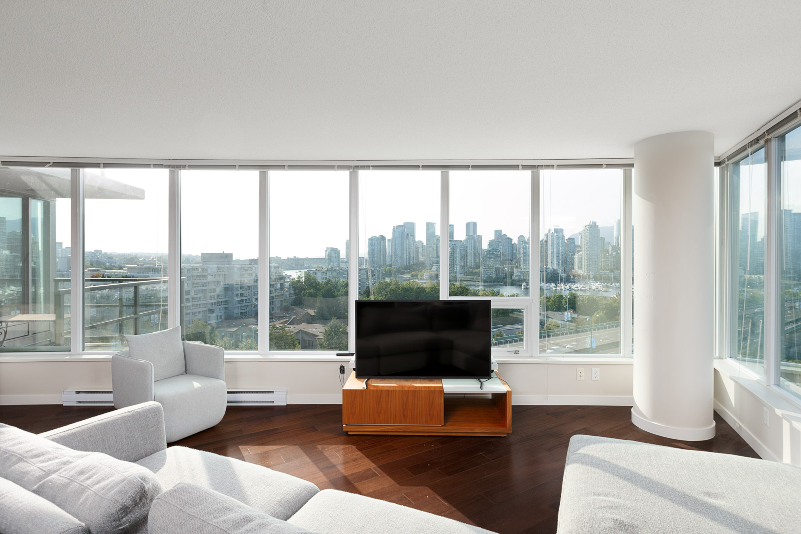White couches surrounding a television overlooking the Vancouver city skyline.