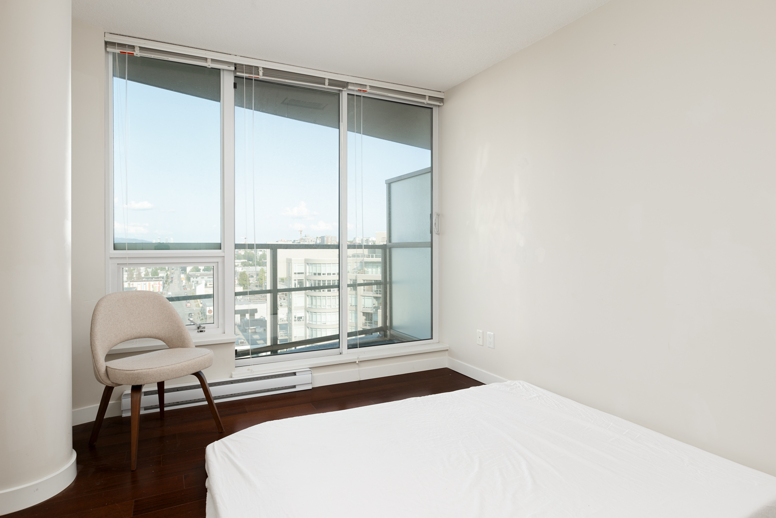 Bedroom opening up onto balcony of Vancouver high rise rental condo.