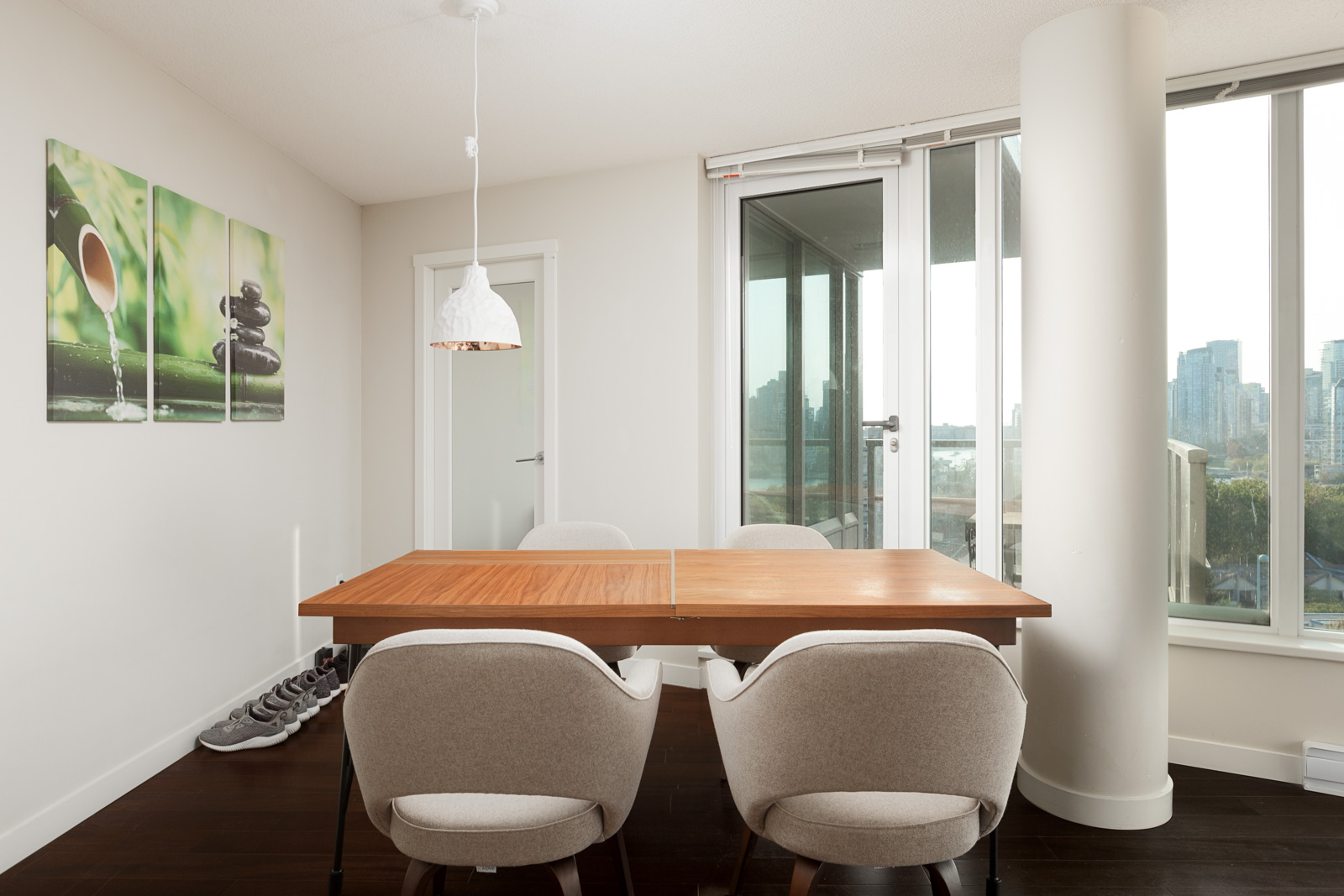 Rectangular wood table with four white upholstered chairs and a single hanging light inside Vancouver luxury rental.