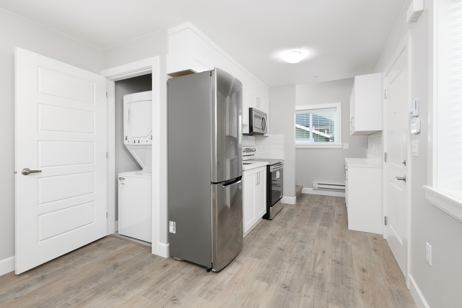 View of washer and dryer closet next to kitchen in Vancouver rental with stainless steel appliances in Vancouver unfurnished rental home..