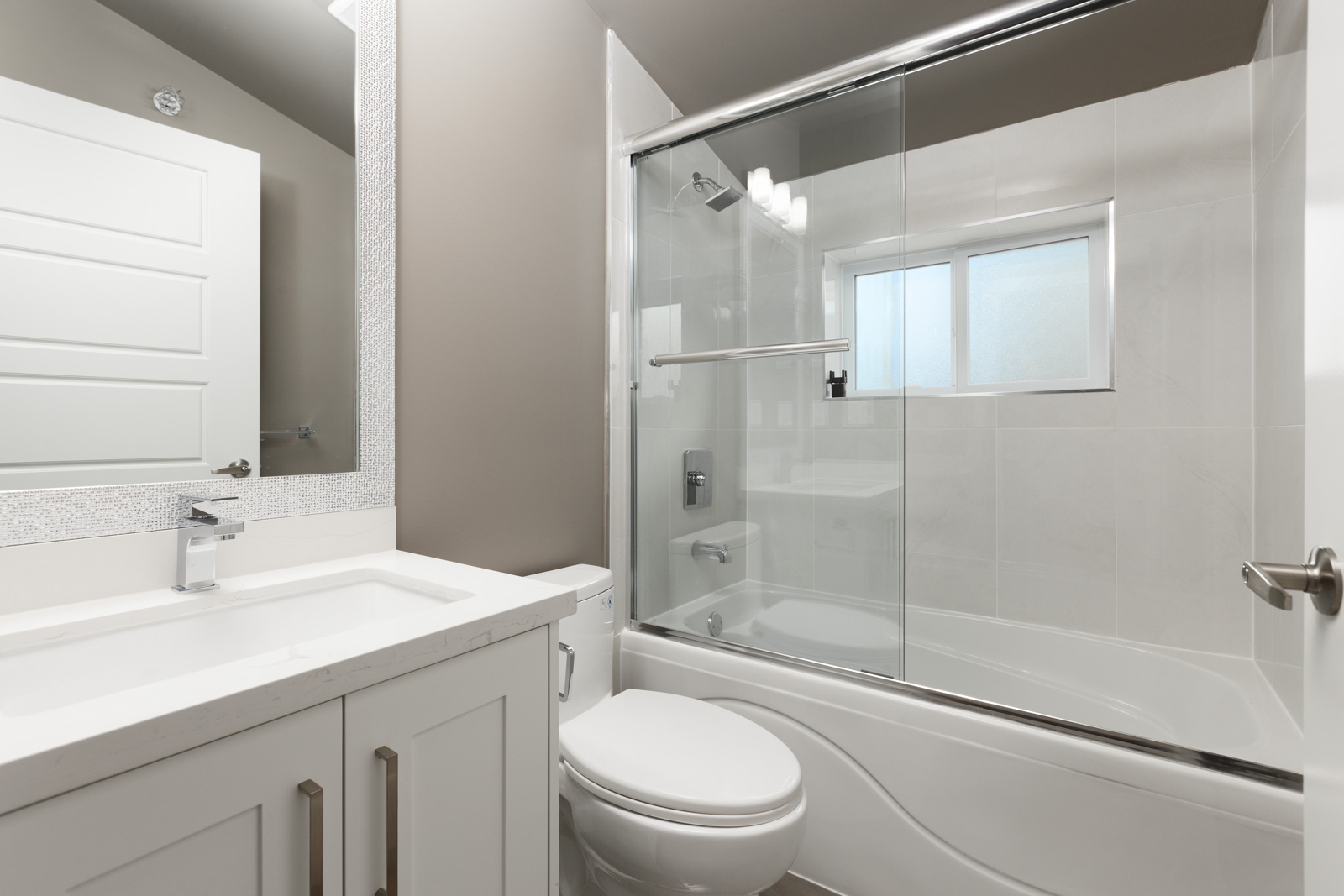 Bathroom with stand up tub and sliding glass shower door inside Vancouver rental home.