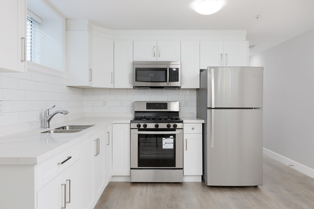 Kitchen with white cabinetry and stainless steel appliances inside Vancouver rental.