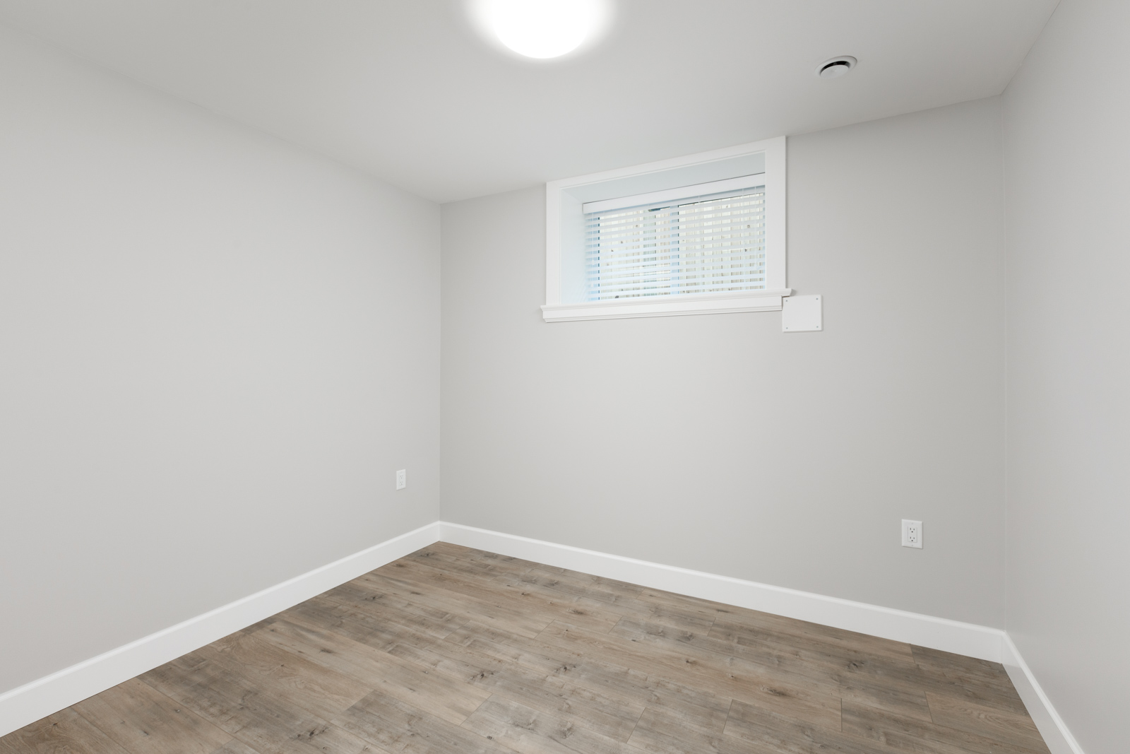 Empty light grey room inside Vancouver rental with ash hardwood and window.