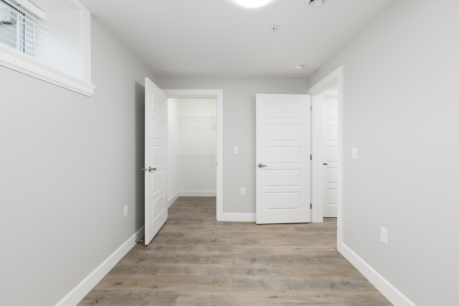 Light grey room with multiple doorways inside Vancouver rental.