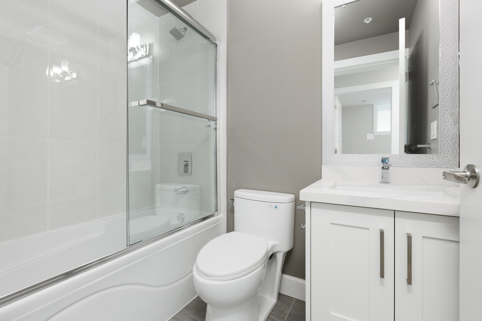 White bathroom with stand up tub and sliding glass shower door inside Vancouver rental..