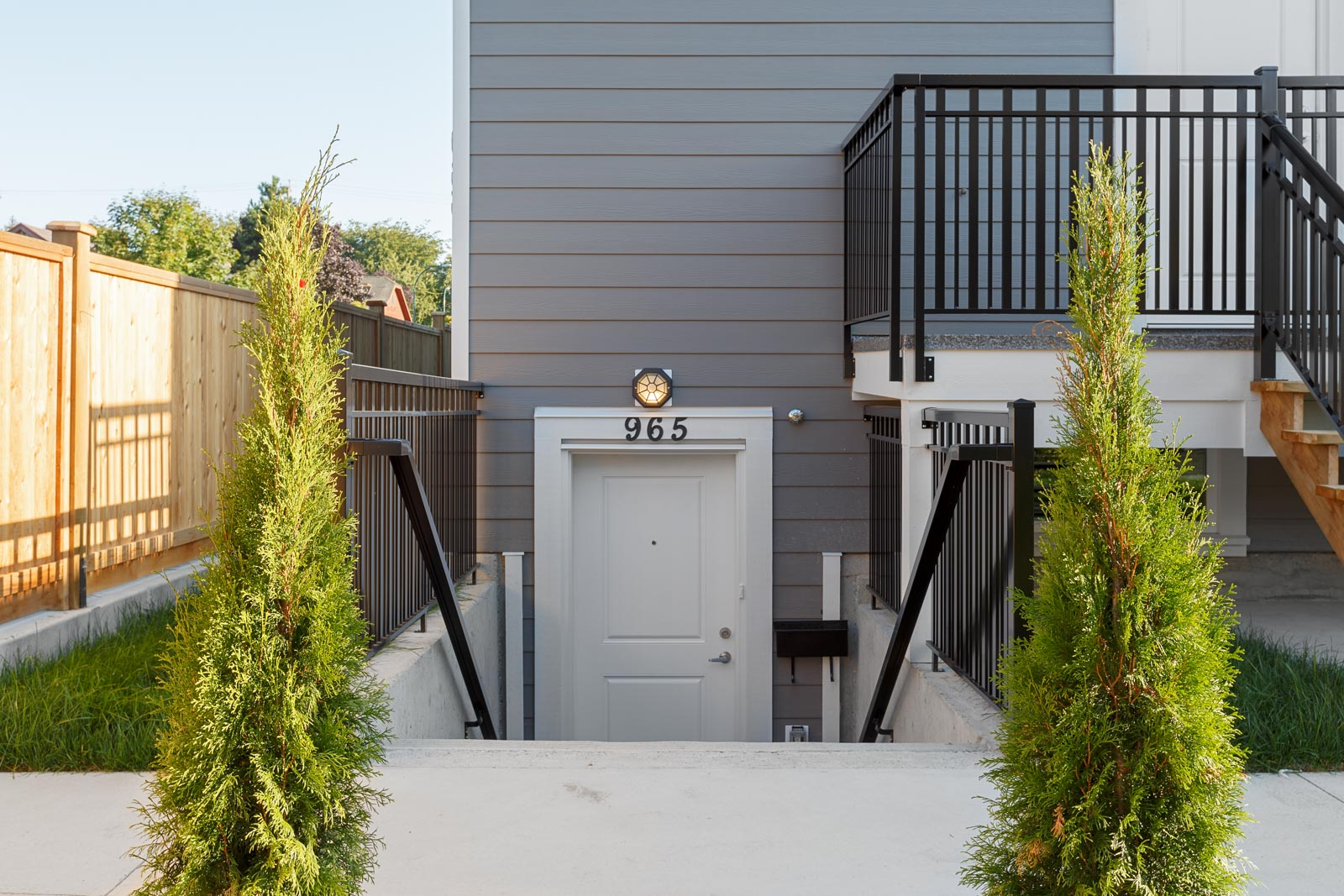 Exterior entrance of Vancouver rental consisting of two small trees surrounding a stairwell to a white door.