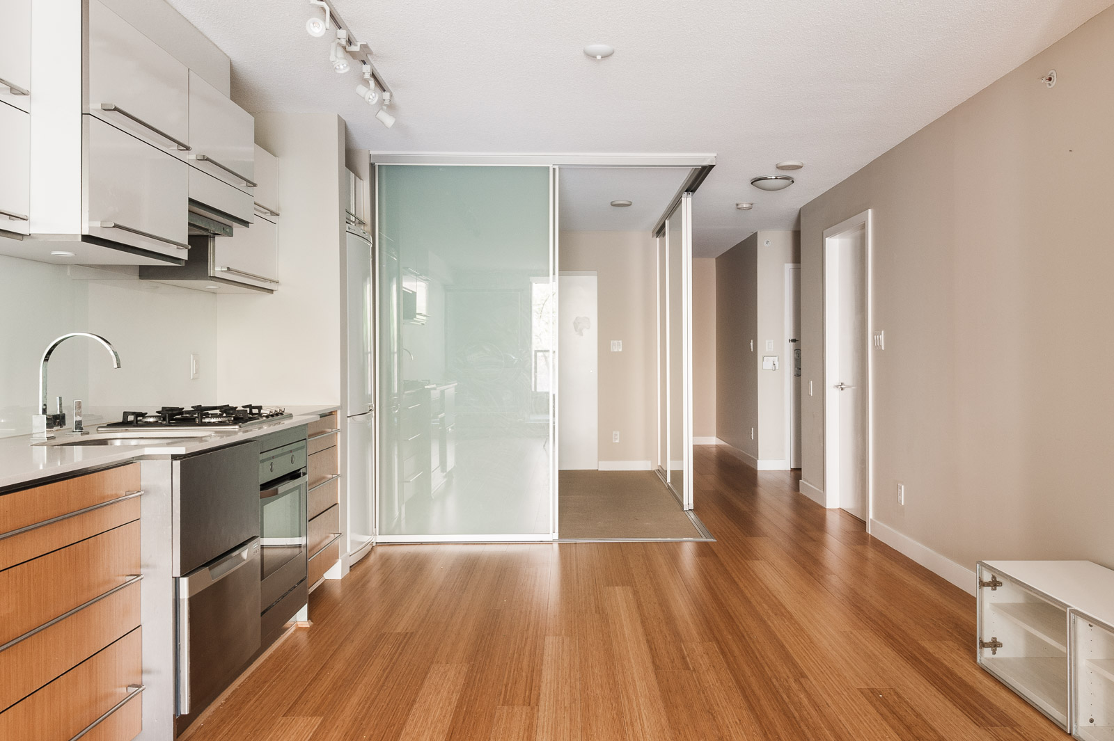 A frosted glass sliding door leads to another bedroom in an unfurnished Vancouver condo rental.