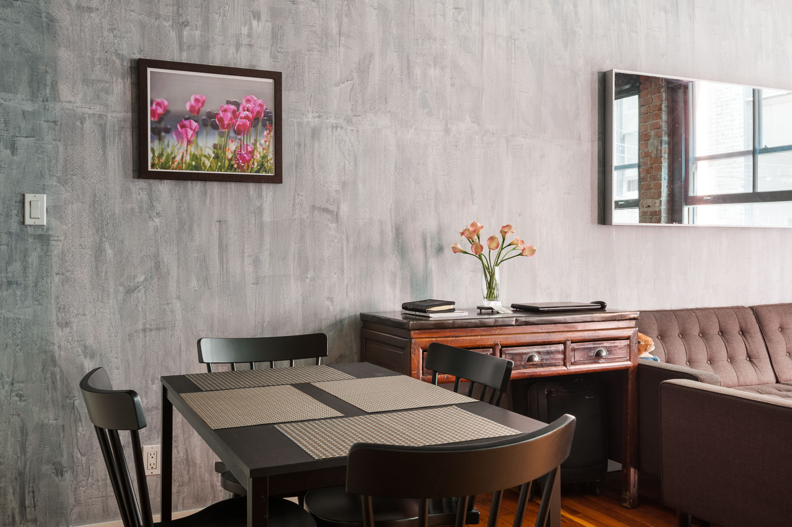 A small dining table beneath a floral painting inside Vancouver rental managed by Birds Nest Properties.