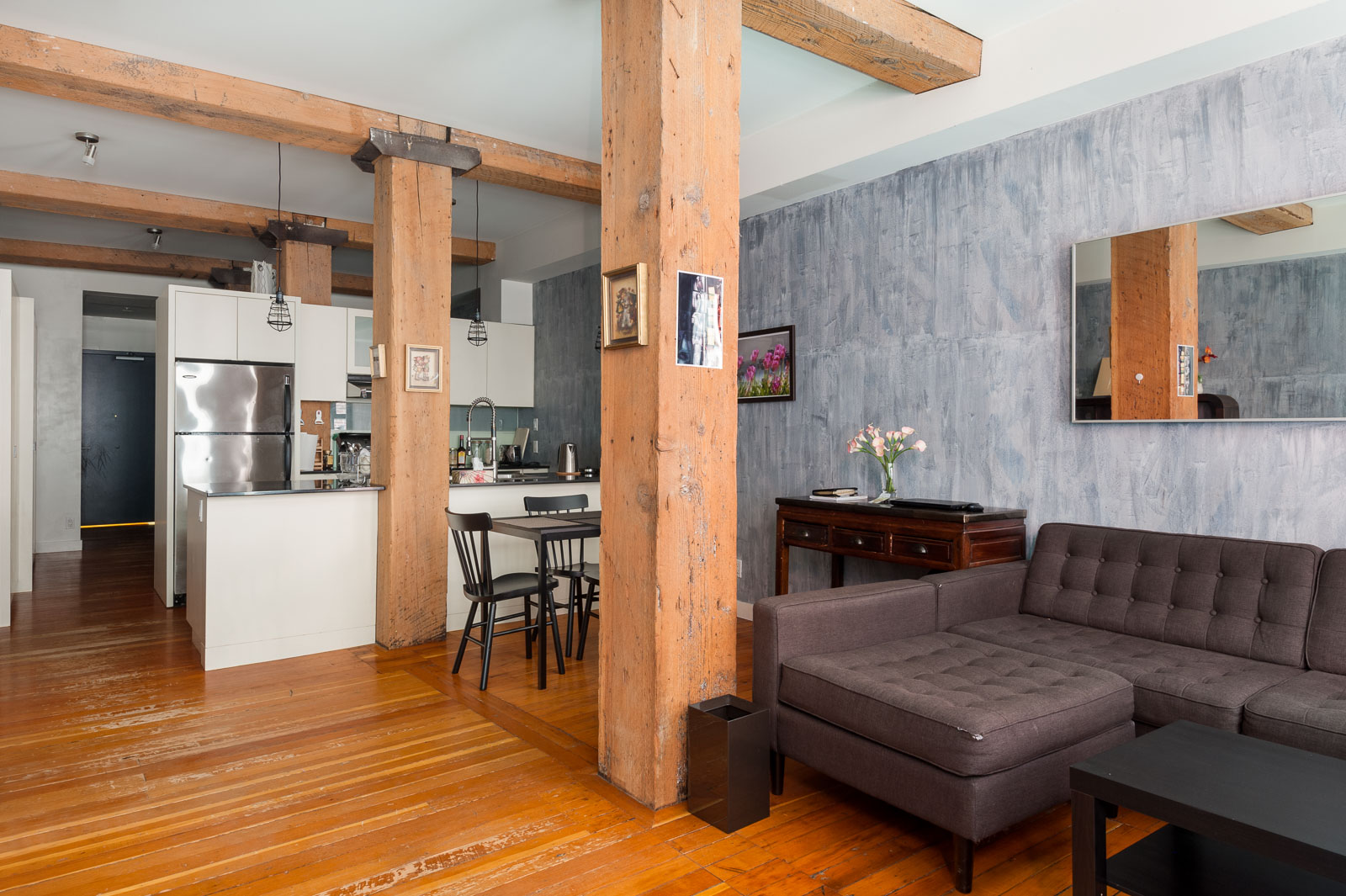 Kitchen in furnished Vancouver rental looks out on living area, supported by wooden beams.