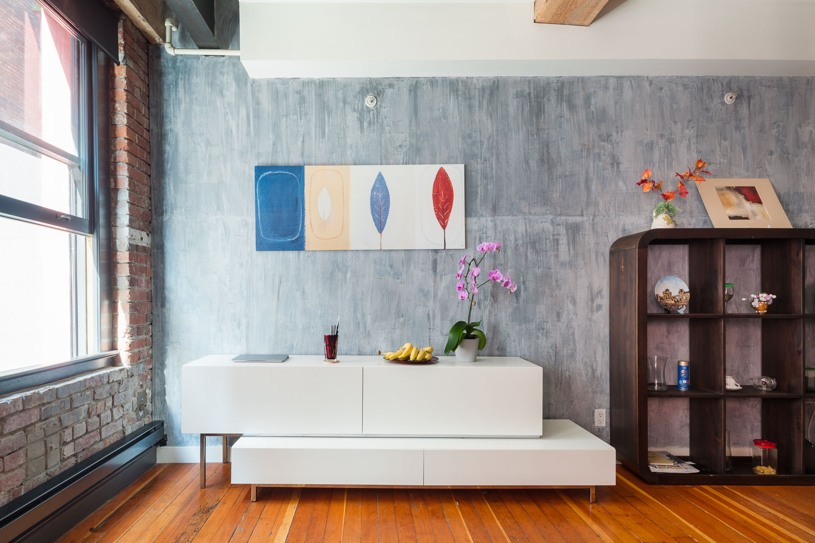 A stretch of steel blue wall with hanging artwork and a boxy white desk underneath inside Vancouver condo rental.