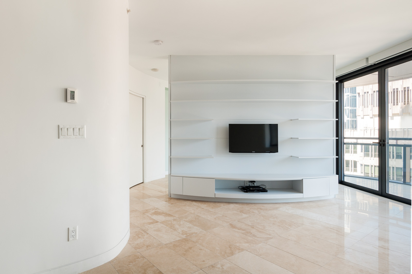 White shelving housing a television in Vancouver luxury rental managed by Birds Nest Properties.