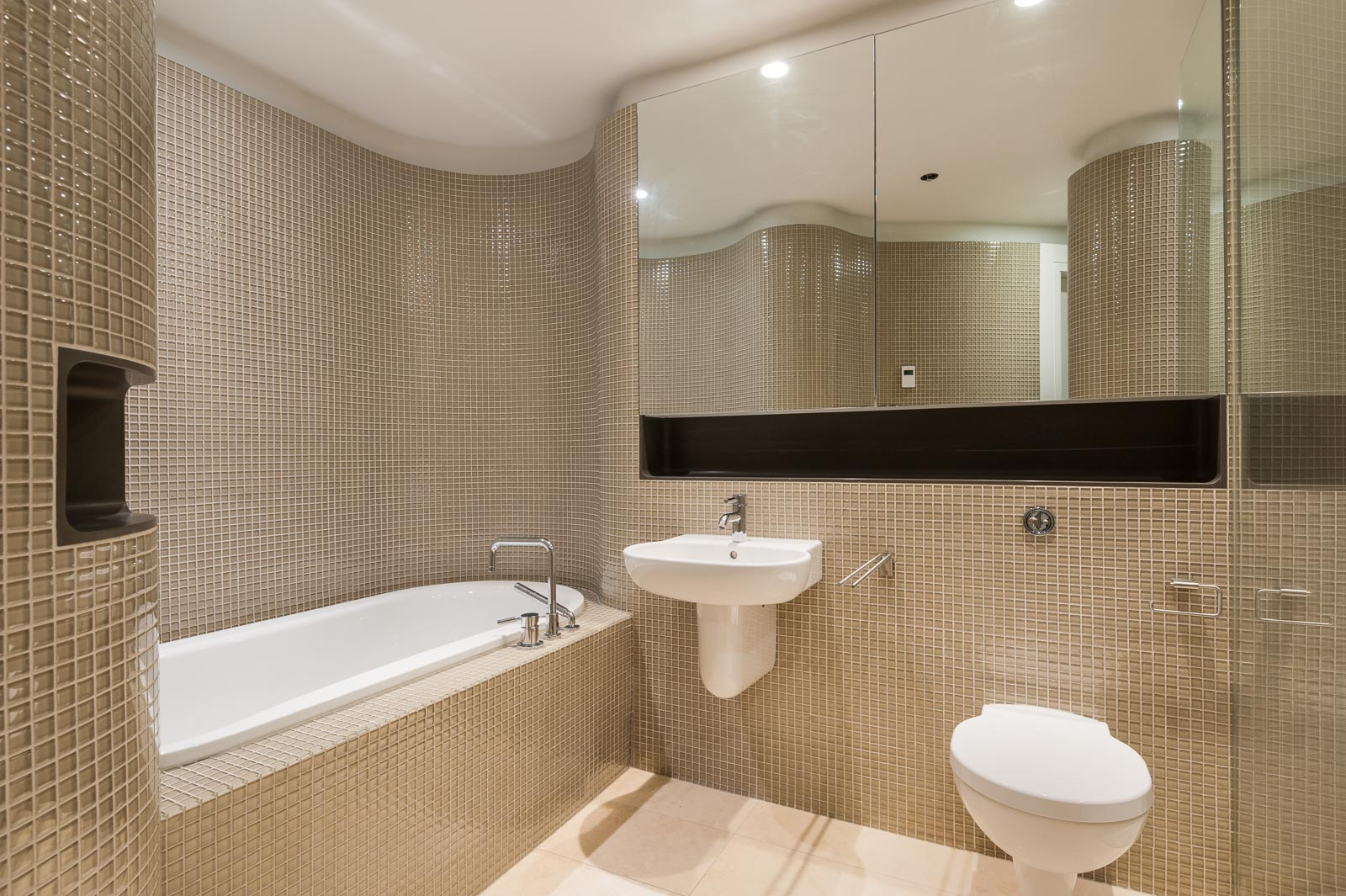 Bathroom with curved, tiled walls and a built-in tub inside luxury Downtown Vancouver rental.