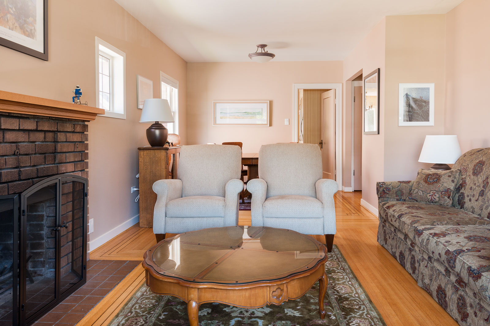 Two chairs behind a circular coffee table in a living room of furnished Westside Vancouver rental home.