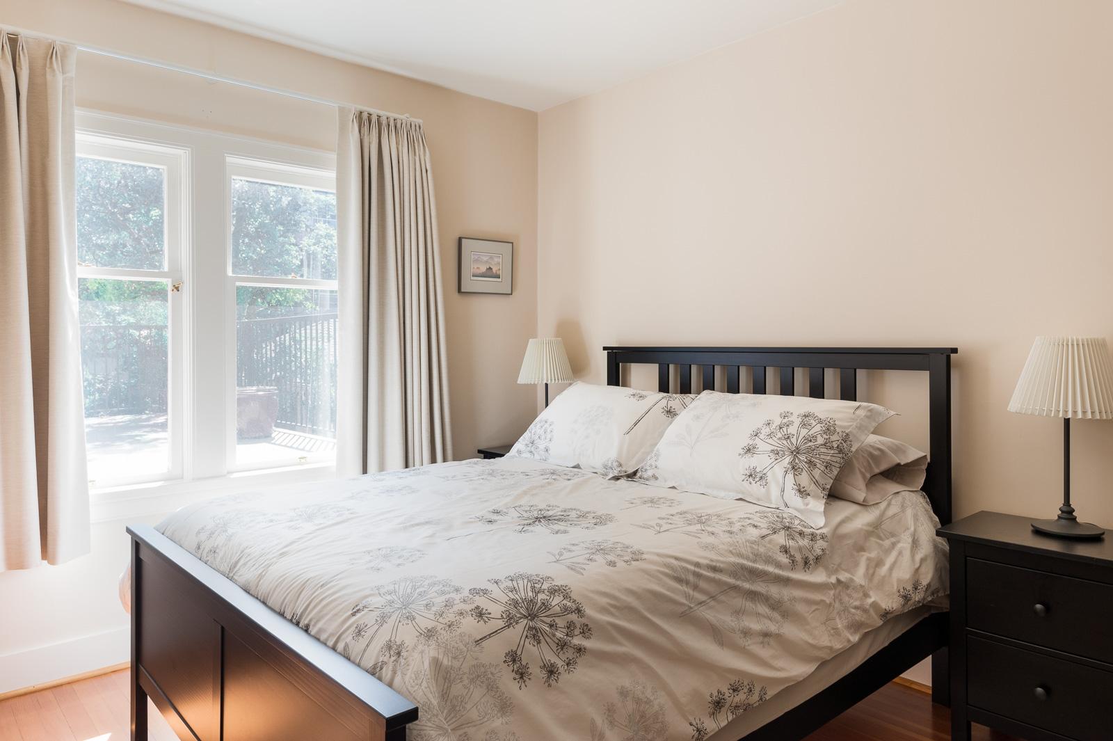 Bedroom with floral patterned bedspread inside Westside Vancouver rental managed by Birds Nest Properties.