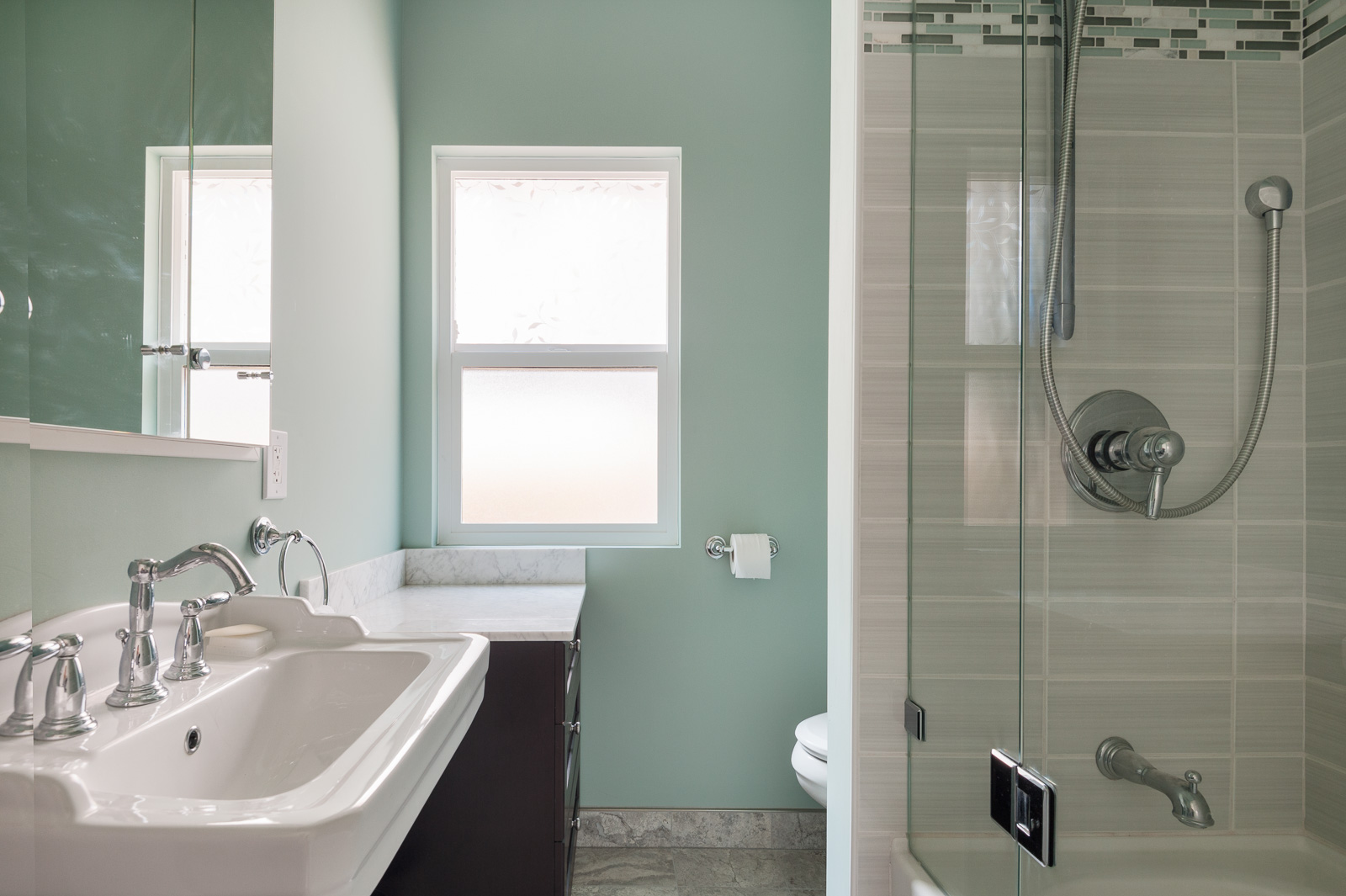 Light green bathroom with dark hardwood cabinetry and a stand-up tub inside Westside Vancouver rental.