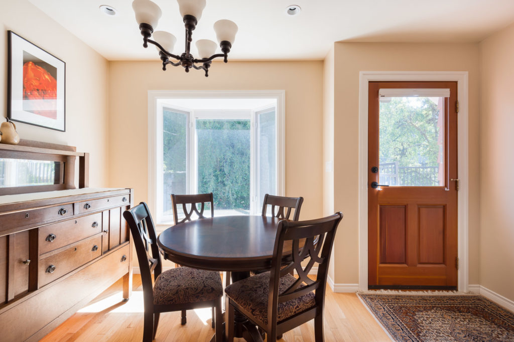 Dining room with circular, wooden table and four chairs inside Westside Vancouver rental listed by Birds Nest Properties.