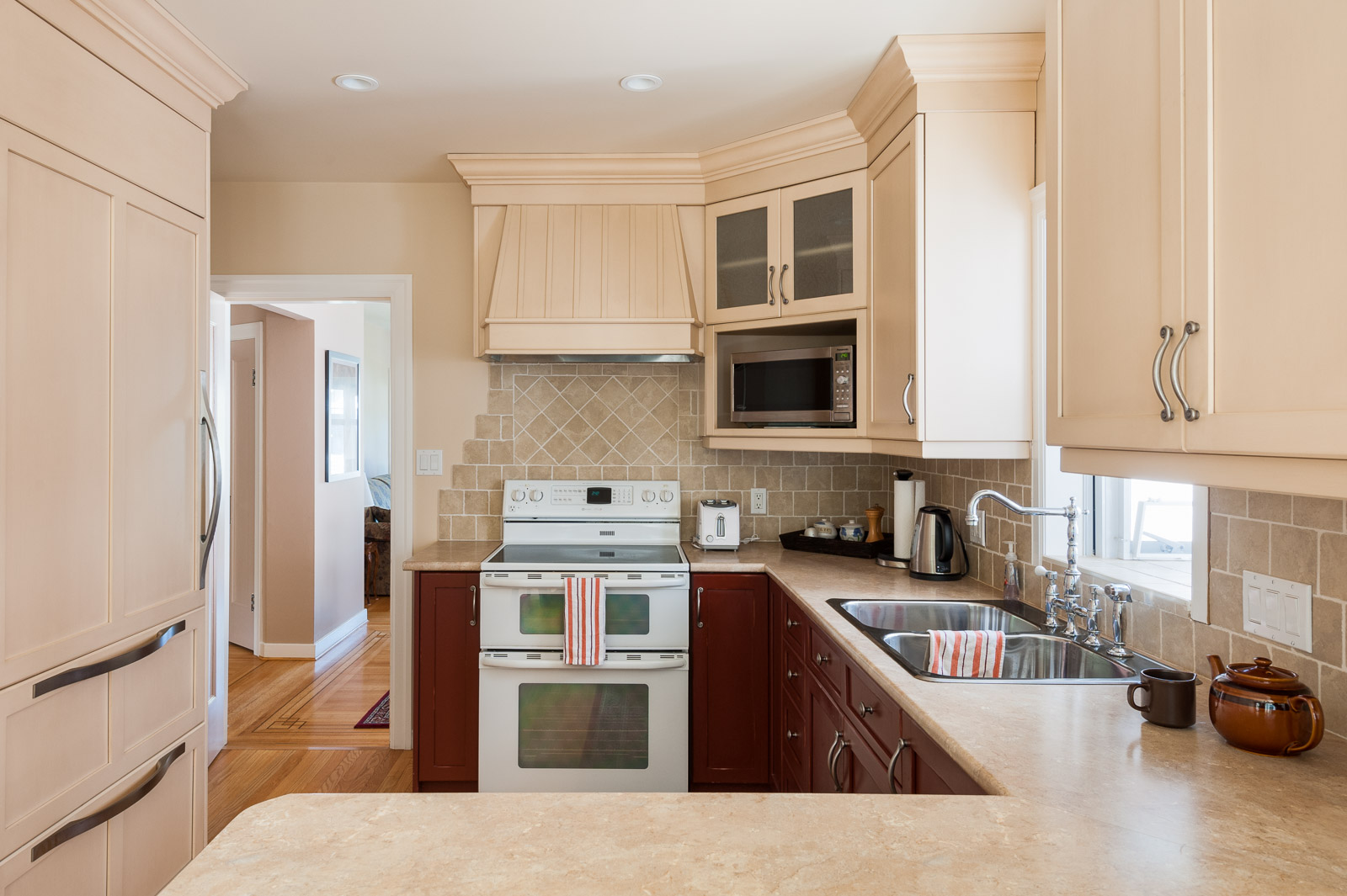 Kitchen with cherry wood cabinetry and marble counter tops inside Westside Vancouver rental managed by Birds Nest Properties..