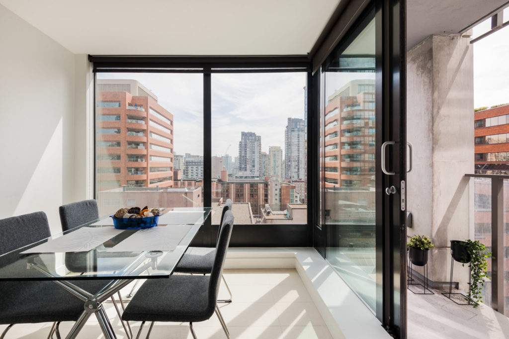 Glass dining table with four black chairs overlooking Vancouver from luxury rental.