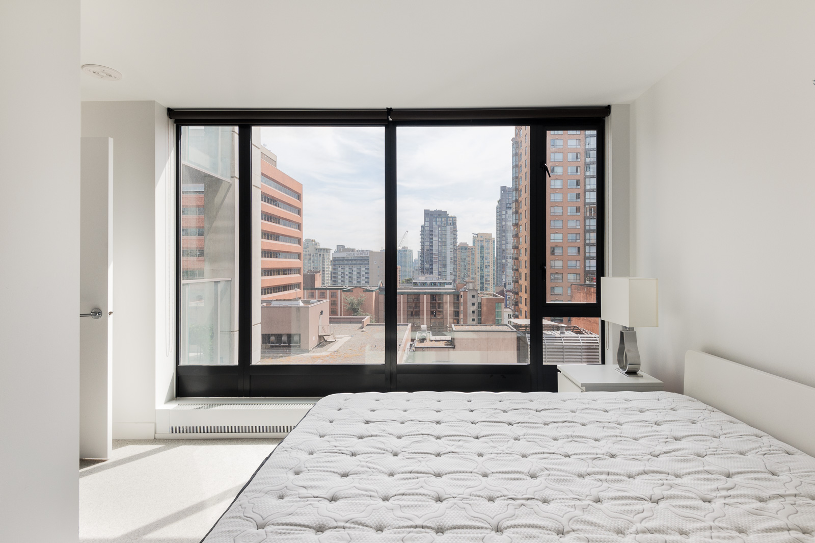 Bedroom in luxury rental with floor-to-ceiling windows offering view of Vancouver.