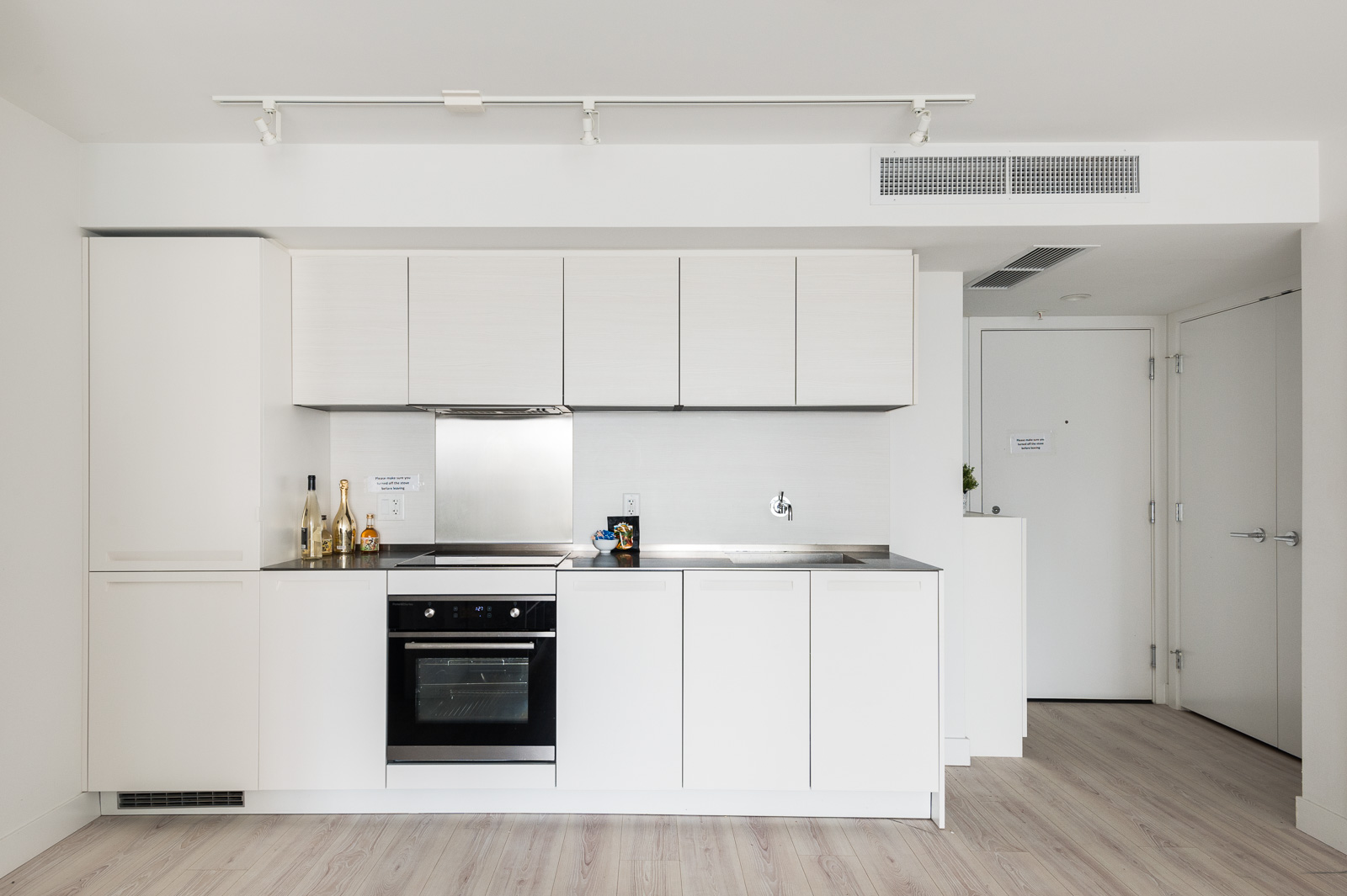 Kitchen decorated in ash hardwood and white cabinetry with built-in stove top oven in Vancouver luxury condo.