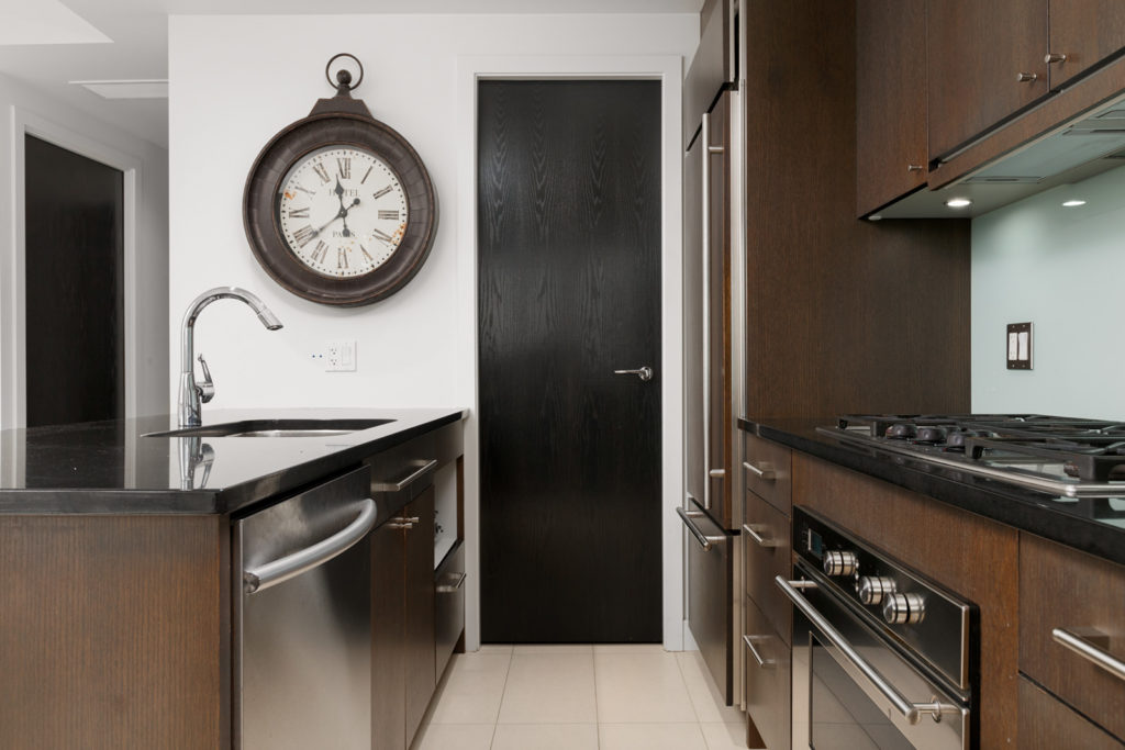 Condo kitchen with clock dishwasher stove and dark door