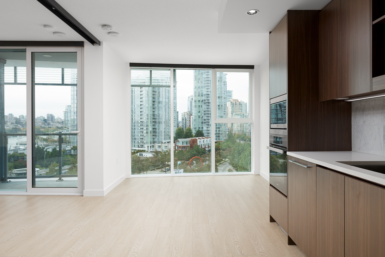 floor to ceiling window in living room of rental condo with kitchen on right