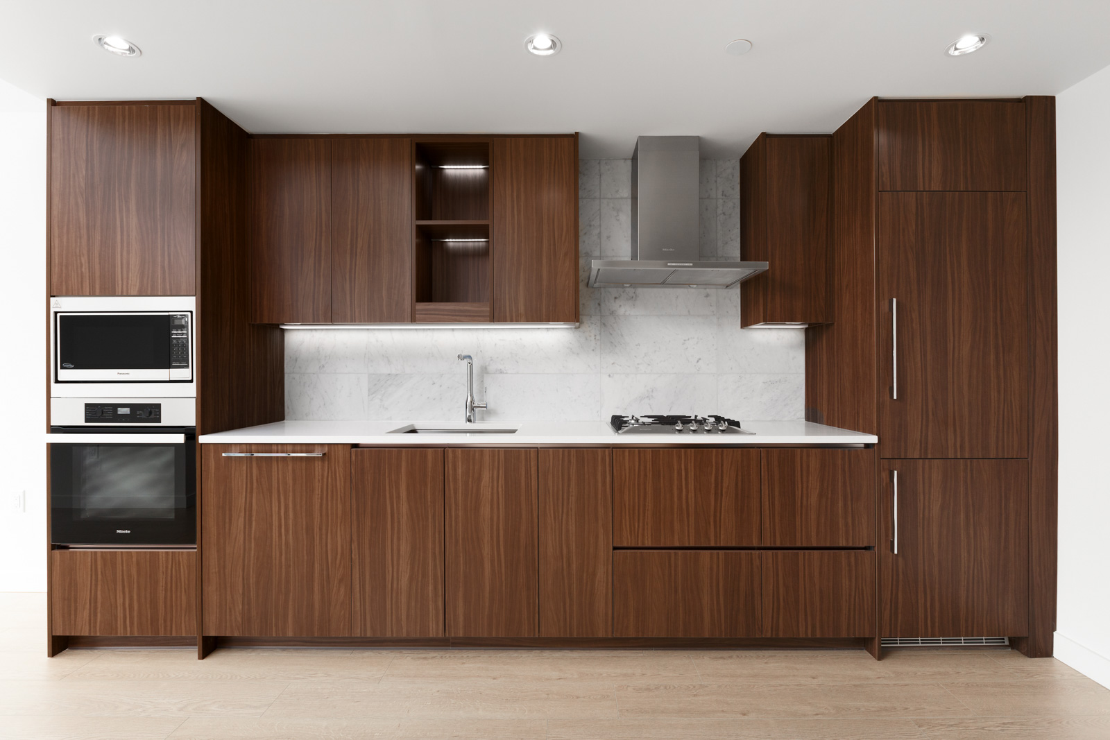 kitchen with dark wood cabinets along the wall of rental condo at arc vancouver building