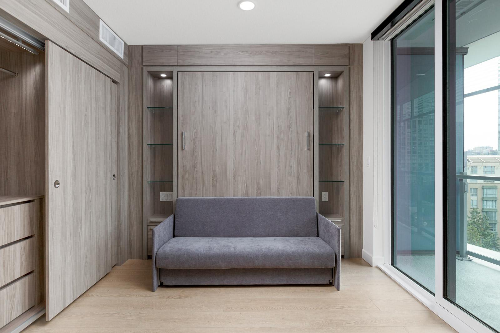 murphy bed sofa in bedroom of arc rental condo with dark wood wall