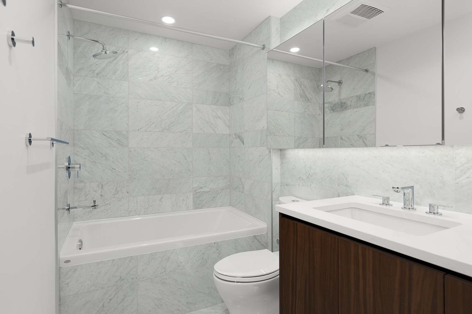 bathroom with marble tiling showing bath tub toilet basin and mirrors