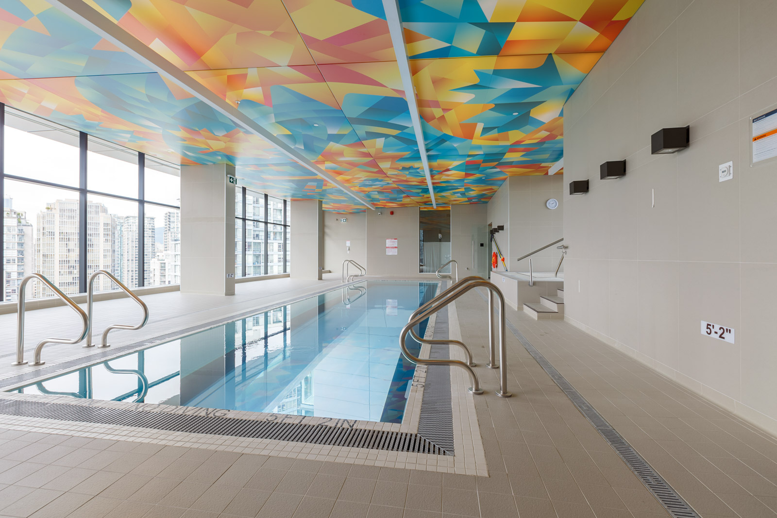 indoor pool in the arc condo building in vancouver with colourful ceiling