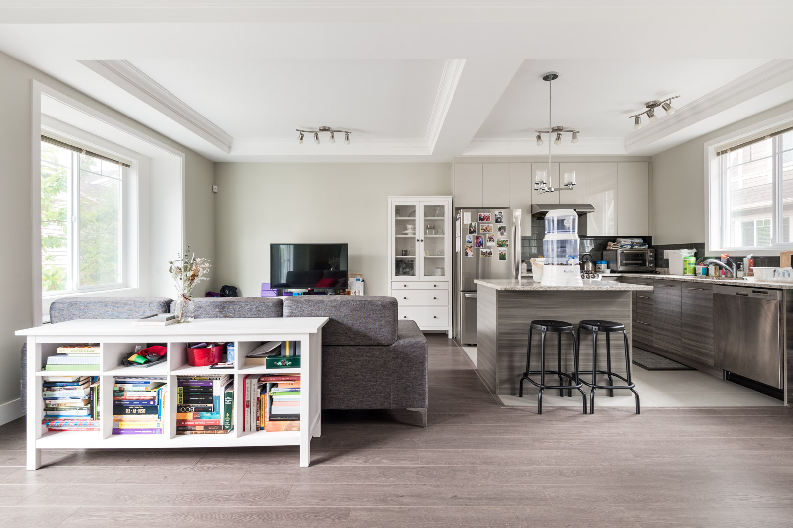 condo living room with white shelving table behind grey couch