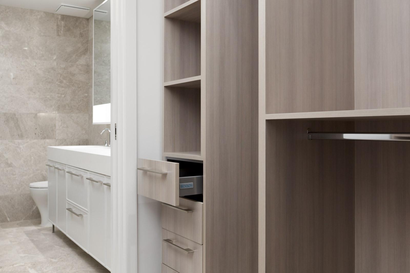 condo closet with dark wood shelves beside bathroom