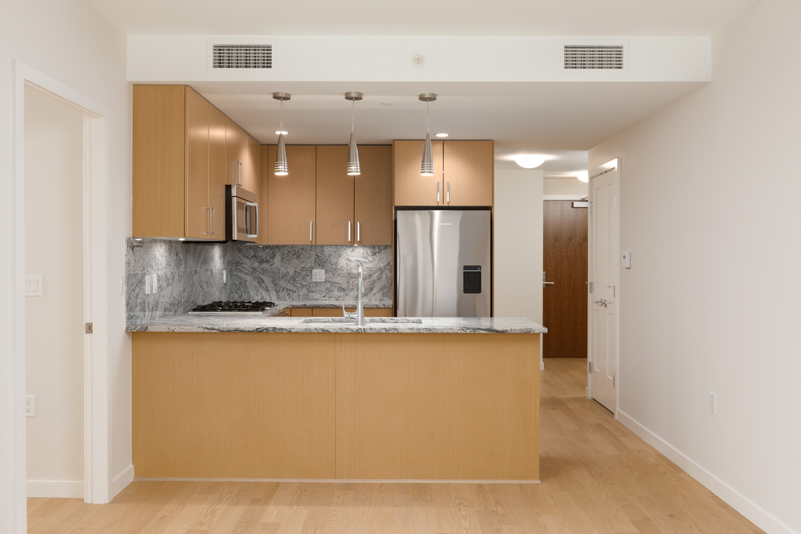 open kitchen in rental condo with wood cabinets and pendant lights