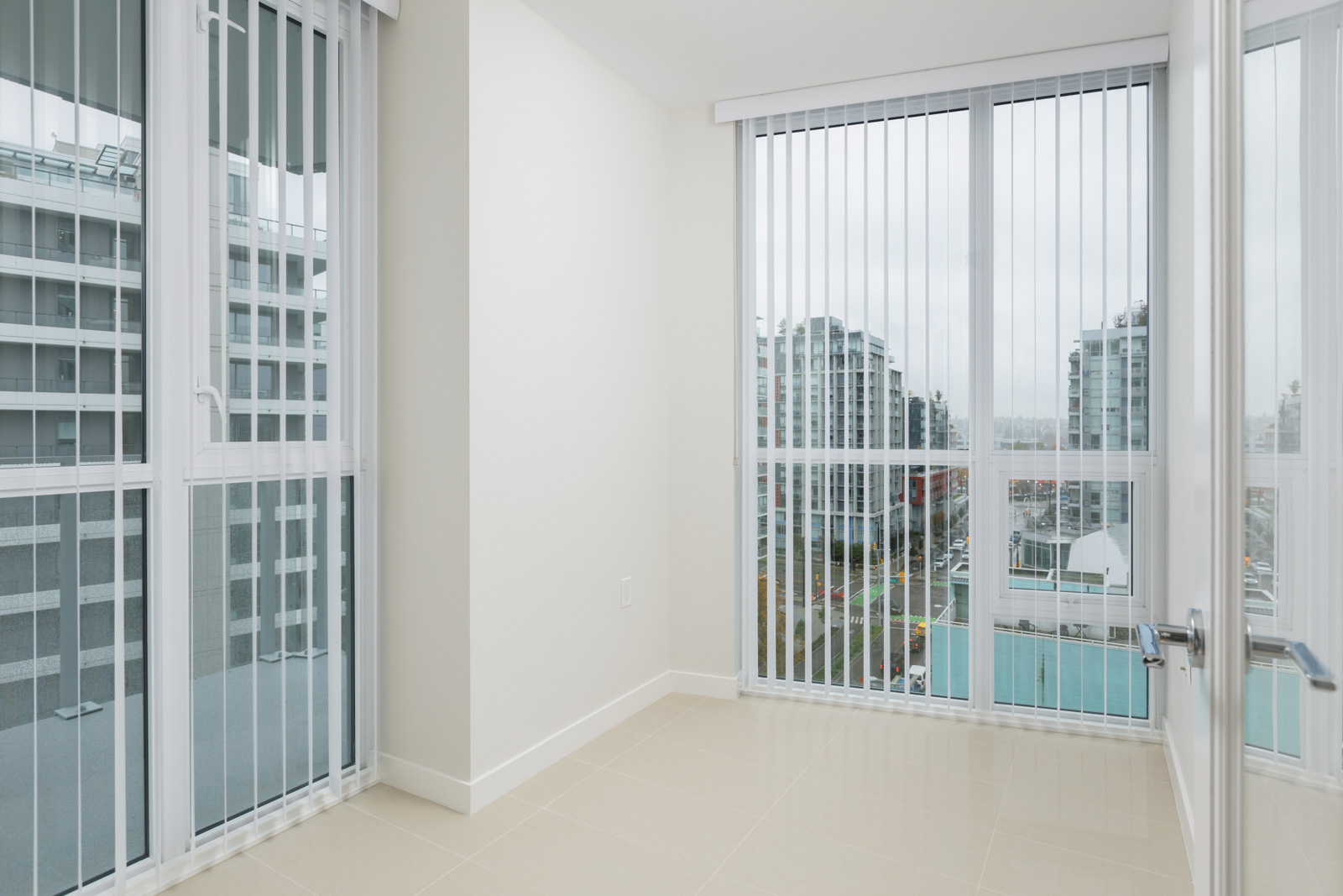 windows with open blinds in living room of condo