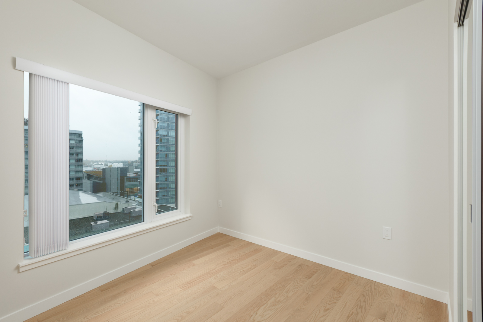 room with white walls and light hardwood floors and window