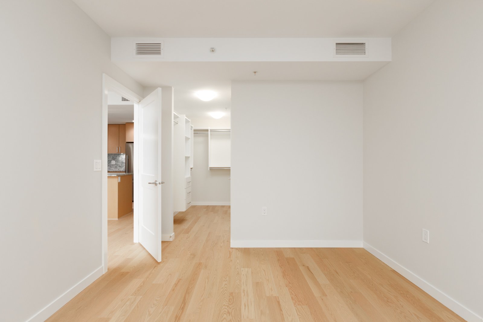 room with white walls and light hardwood floors
