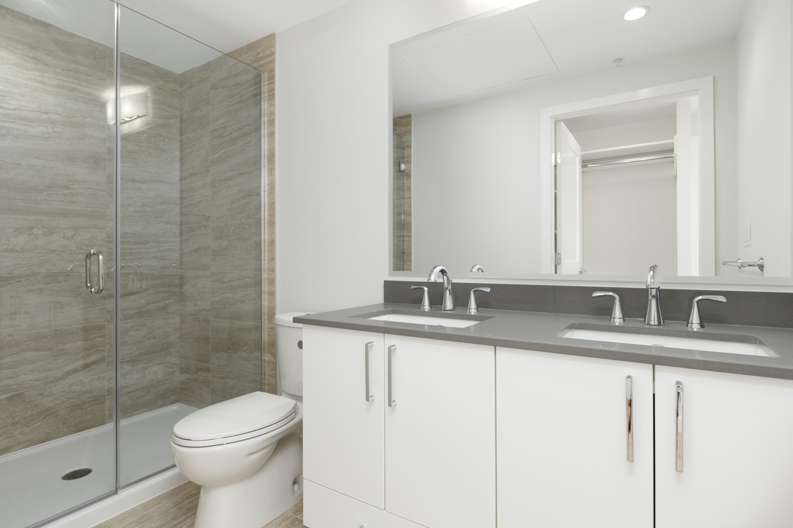 bathroom in condo with grey countertops mirrors grey tiles and toilet