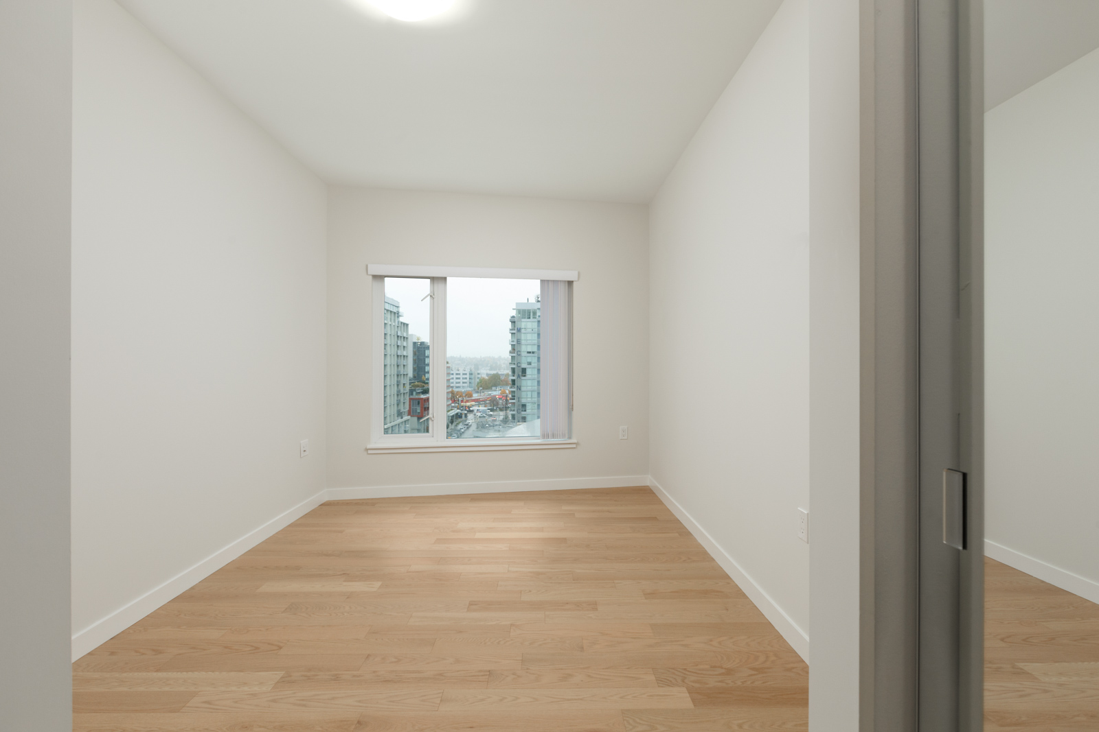 empty room in vancouver rental condo with white walls windows and hardwood floors
