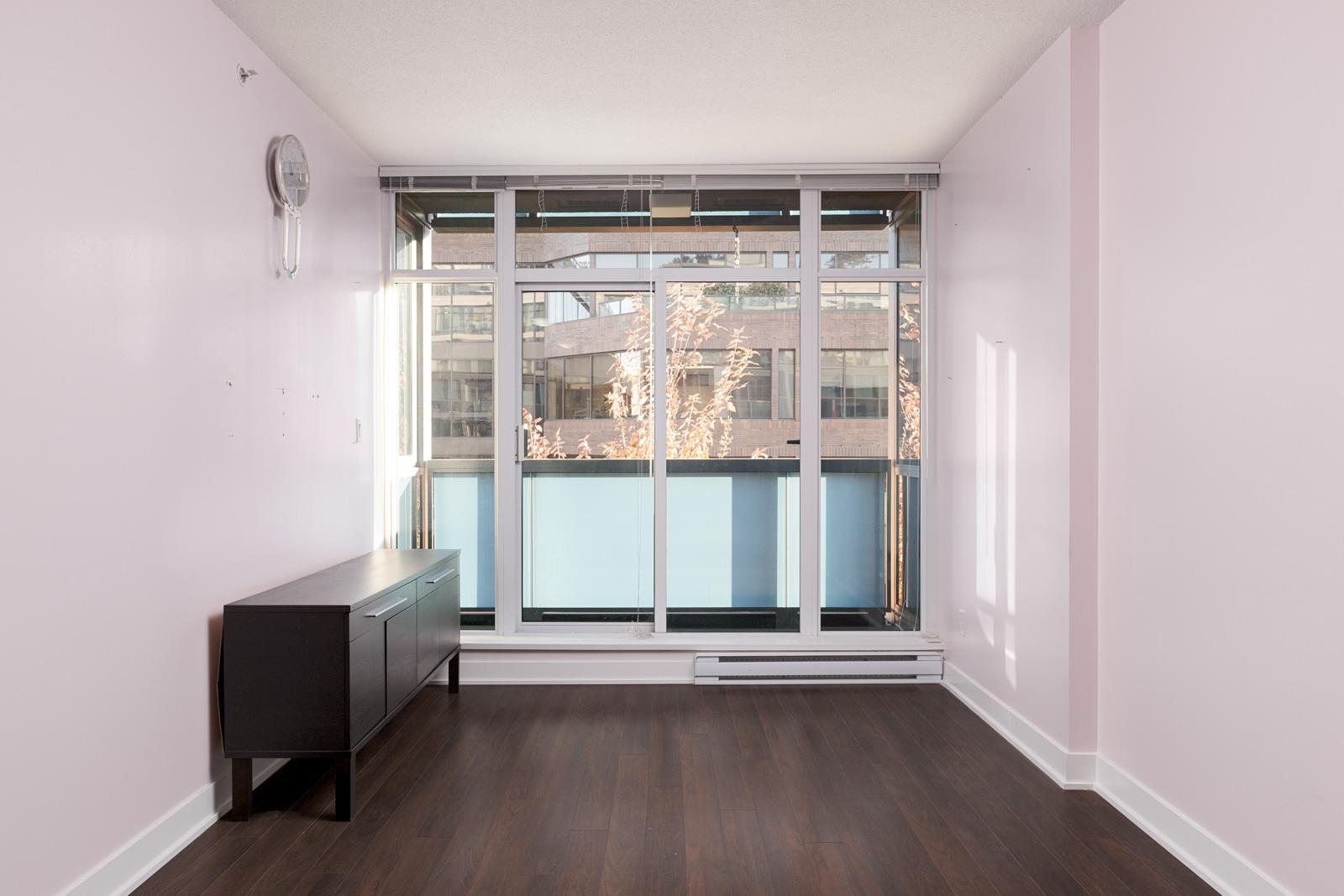 Living room with windows and dark hardwood floors in Kits360 condo rental