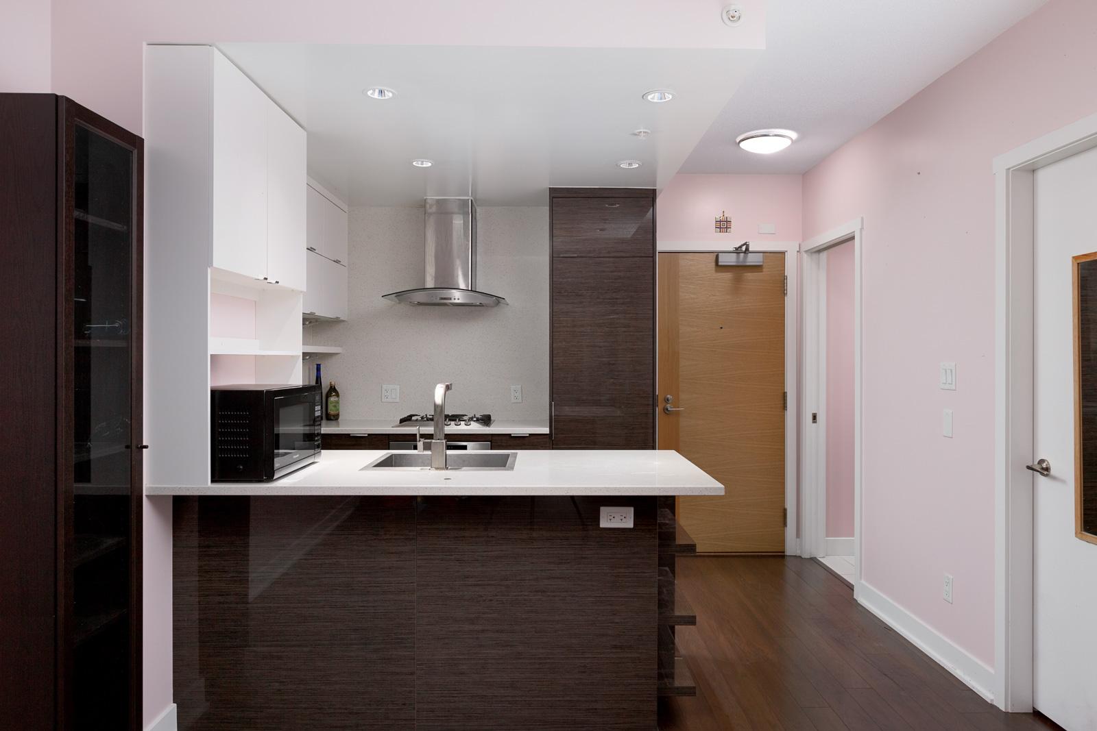 Kitchen with dark hardwood floors in Kits360 condo rental