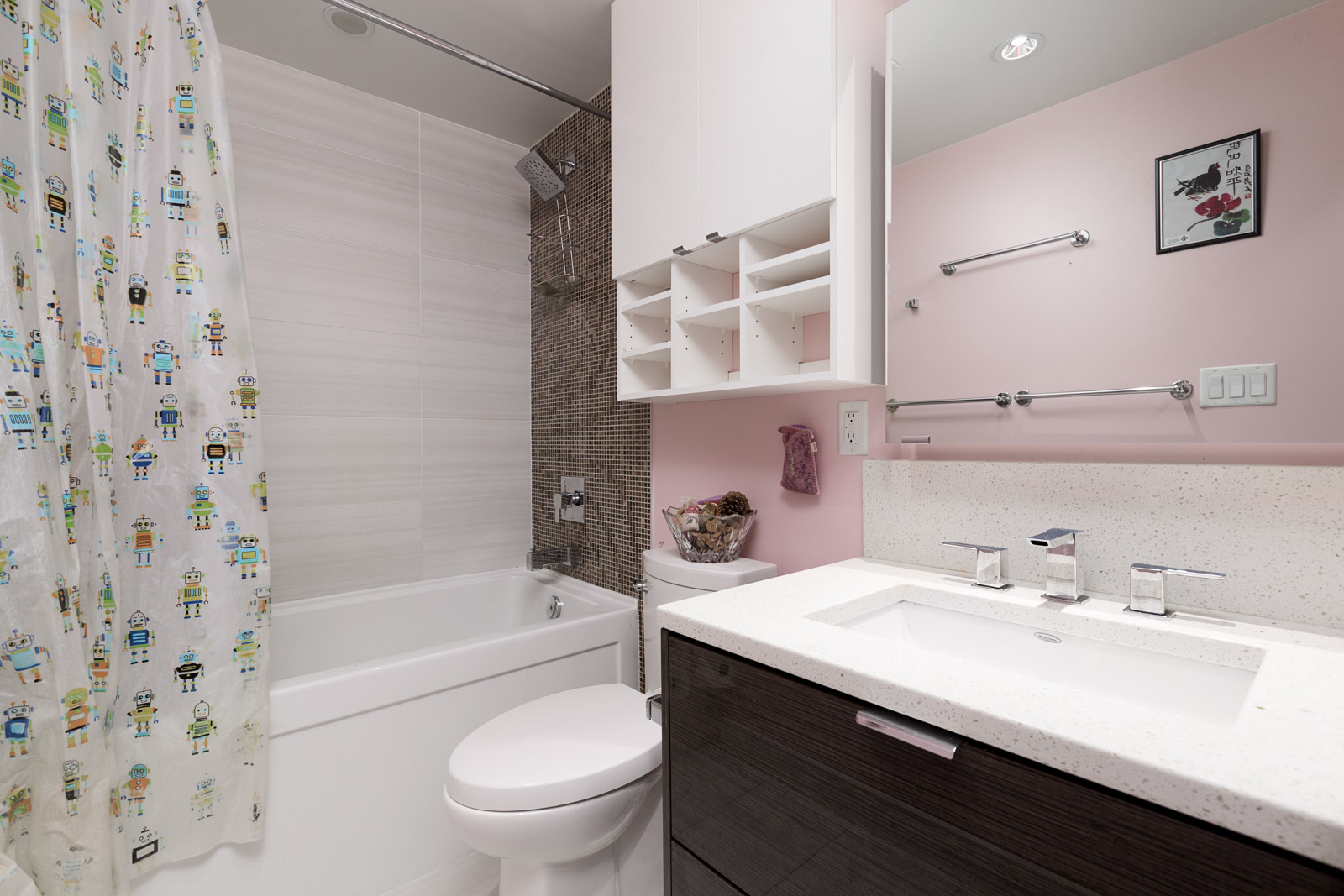 Bathroom with toilet, bath, tiled walls, and vanity and mirror with dark cabinet doors