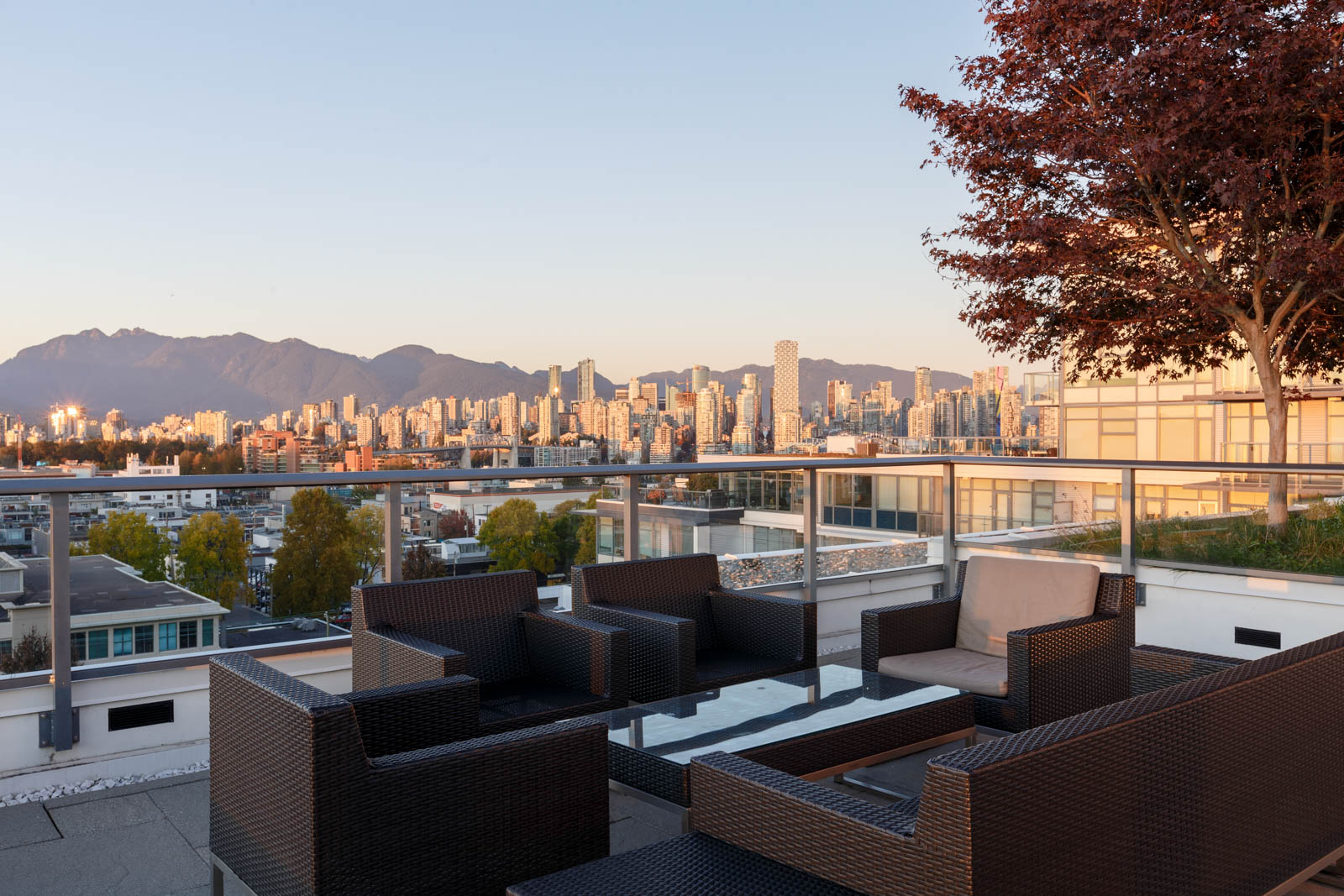 View of Burrard inlet and rooftop patio tables and chairs from Kits360 condo building in Kitsilano and Fairview