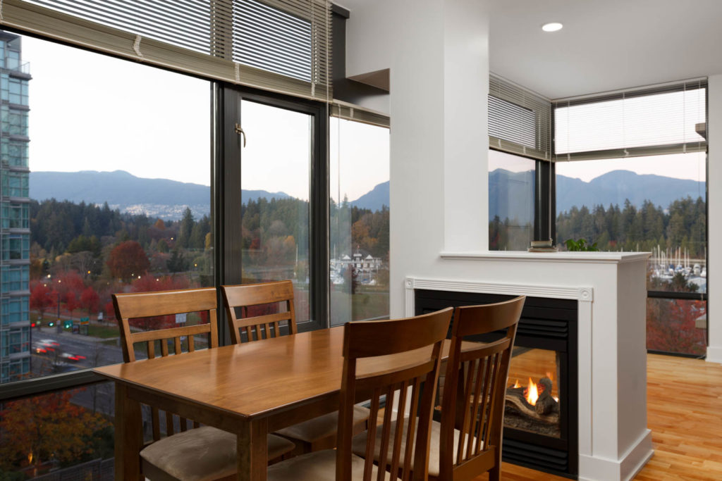 dining room with wood table and chairs in lumiere rental condo with view to outside of coal harbour and stanley park