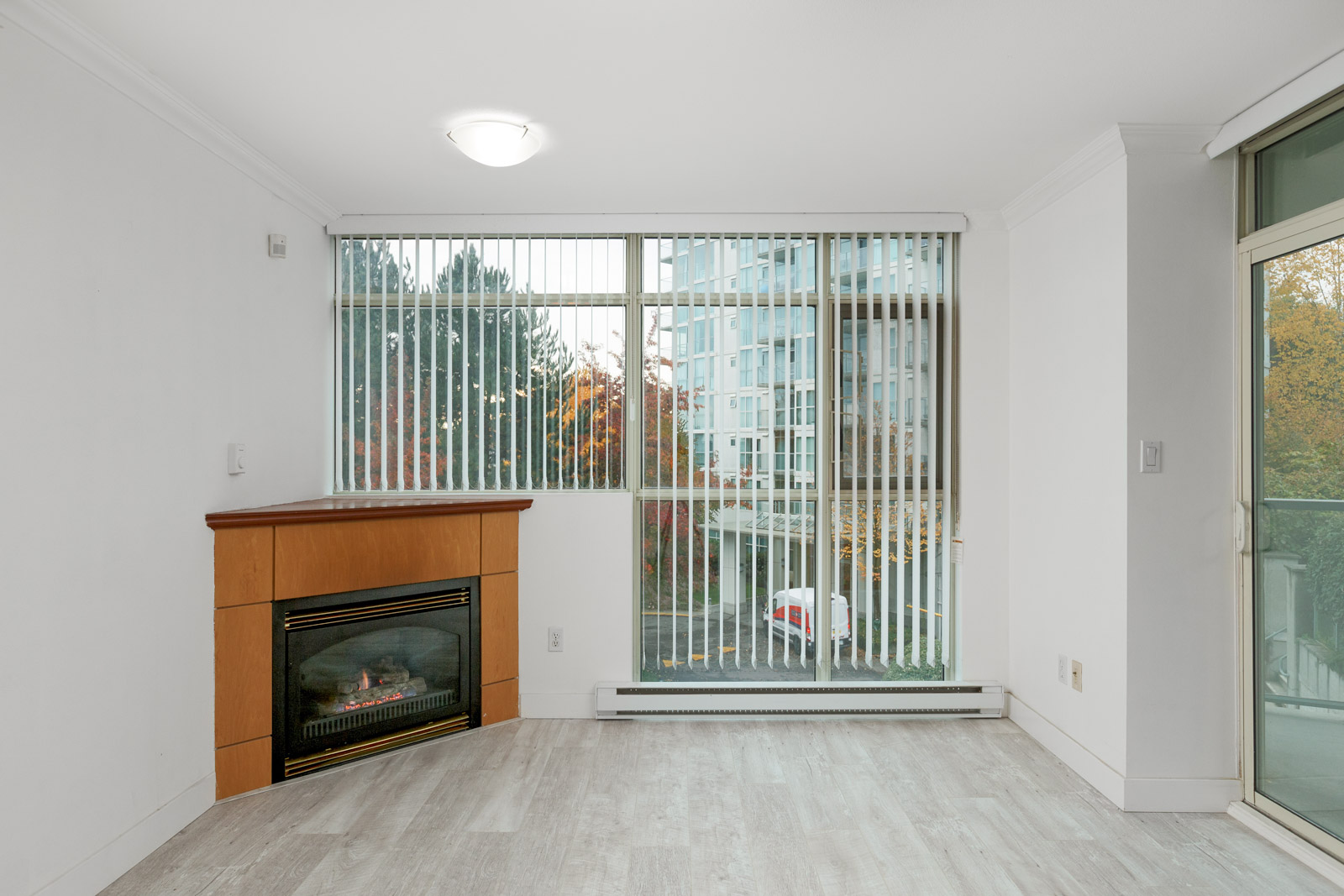 Unfurnished living room with fireplace and hardwood floors in River Dance building in River District East Vancouver rental condo property