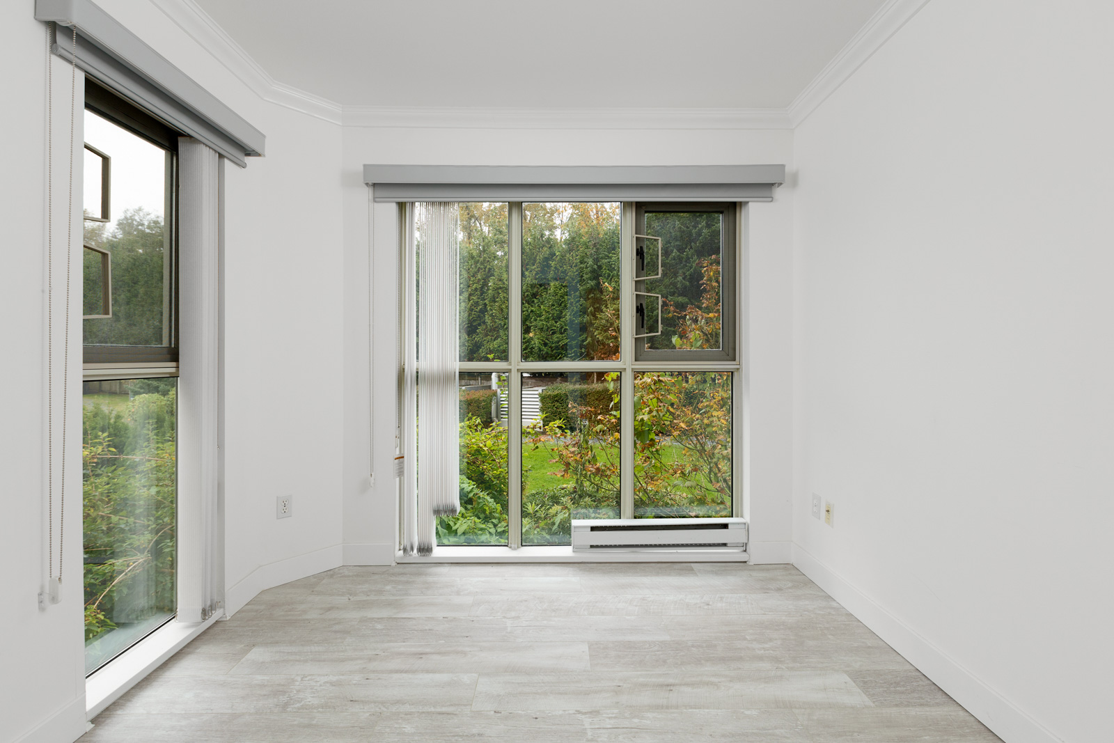 Unfurnished bedroom with floor to ceiling window view of outdoor garden in River Dance building in River District Vancouver rental condo property
